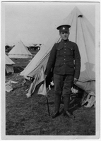 Photograph of  soldier [at camp] holding flag