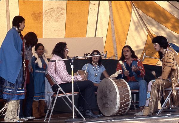 Image of men and women in regalia seated around a drum.