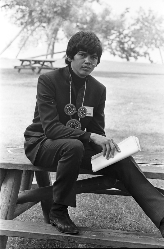 Image of young man in dark suit wearing beaded medallion necklace holdong a sheaf of paper. He is seated on an outdoor lunch table.
