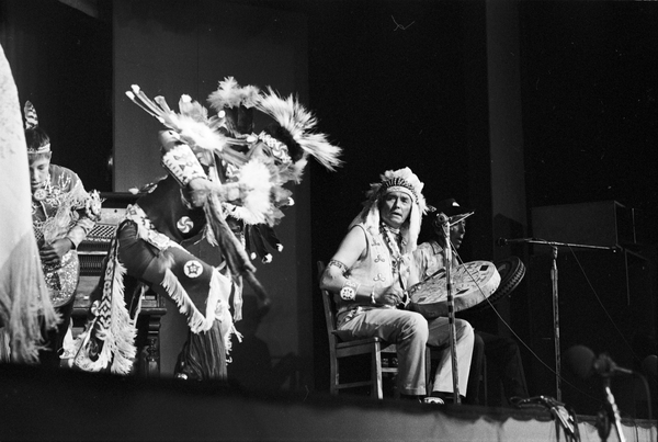 Two young First Nations men performing the Chicken Dance, with two hand drummers on stage, at the Mariposa Folk Festival in 1970.