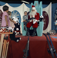 Image of Santa with Paul Watkinson (seated), Laurie Brooks (peach dress), and Margie Schnurr (pink dress) at Santa's Ice Palace in Christmas Fairyland at the Queen Elizabeth Building, Exhibition Place.