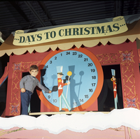 Image of a little boy next to Santa's countdown to Christmas clock at Santa's Ice Palace in Christmas Fairyland at the Queen Elizabeth Building, Exhibition Place.