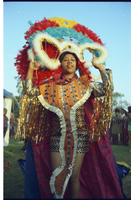 Female mas camp dancer wearing feathered headdress (white, blue, red & yellow) with an orange chest covering with white fringe; Caribana costume judging on Centre Island.