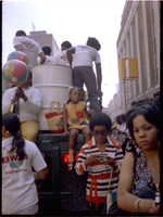 Woman and two children take a ride on the steel pan truck