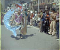 Crowd of men, women and children watch individual masquerader in large costume
