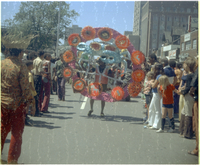 Crowd of men, women and children watch individual masquerader portray zodiac signs