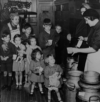 In the baggage car of a train bound for areas safe from diabolical pilotless planes, children line up for milk distributed by members of the British Women's Voluntary Services