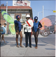 Bermudian police officer standing with Caribana mas players on the corner of Bloor Street and Pauline Avenue.