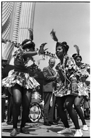 Female mas camp dancers onstage at Nathan Phillips Square, dancing to The Tradewinds band as Mayor William Dennison looks on; Caribana.