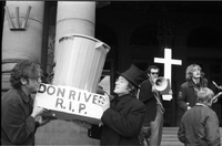 "Demonstration on the steps of the Ontario Legislative Building, two members of Pollution Probe, from the University of Toronto, lifting a trash can with memorial sign ""Don River R.I.P.,"" a man in the background uses a megaphone, a saxophonist for the Lady"