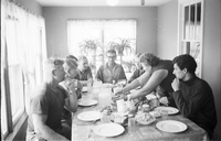 Woman serving food to eight German students in kitchen of Follmer farmhouse in Delhi, Ontario.