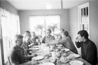 Eight German student labourers at kitchen table, full of food, at the Follmer farmhouse in Delhi, Ontario.