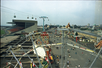 Aerial image of Conklin midway at the CNE, ferris wheel in foreground and Alpine Way cable cars, and stadium in background.