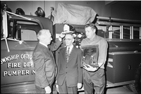 Retiring Toronto Township Fire Chief, Jack Braithwaite (centre), receives a hat, noting his 32 years of service, from an unidentified man (left); younger man (on right) holds a plaque; fire engine in background.
