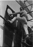 "Sculptor, Walter Yarwood, climbs on scaffolding, hand and foot resting on bronze sculpture, outside Sidney Smith Hall, St. Geoerge Campus, University of Toronto; during the installation of ""Horizon"""