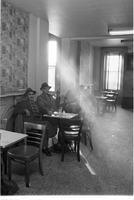 Four men sitting at various tables in the smoky beverage room at The Everene Hotel on Jarvis Street.