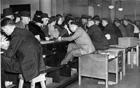 Clerks at Dominion Government Building on Front Street seated on old desks to help customers