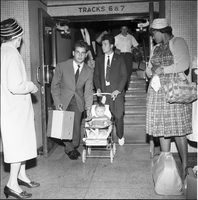Two men, one pushing an infant in a stroller, coming down from track level at Union Station, as two women look on.