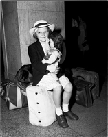 A girl, wearing a hat, sitting on luggage in front of marble column and holding doll in her lap.
