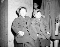 Two boys, wearing coats and matching knitted caps, sitting on luggage next to marble column, with another boy's face in background.