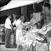 Man and a woman examining the street-side house wares, including fabric, wire buggy, large pickling jars, corn brooms, displayed outside of shop with unmarked awning.