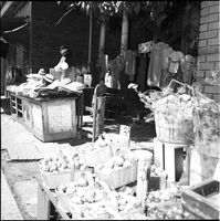 A boy sitting near clothing and housewares including: dresses hanging on line, behind sidewalk display of produce and textiles, and hats.