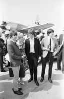 Image of The Beatles members at airport, Ringo, unidentified woman, John and Paul (with camera), plane in background.