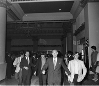 Image of The Beatles members, John Lennon (sunglasses) and Ringo Starr (right), being led through a building lobby by bodyguards.