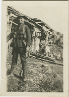 Photograph of soldier in front of run-down structure