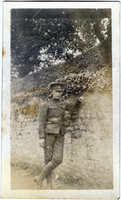 Photograph of soldier leaning against stone wall
