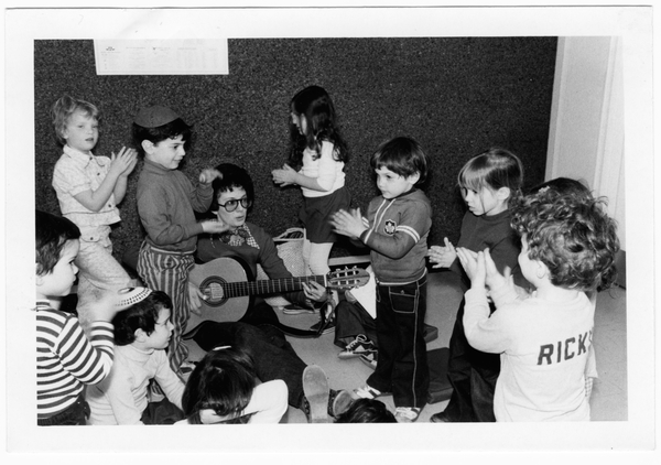 Lois Lilienstein seated on the floor performing on guitar surrounded by children clapping along.
