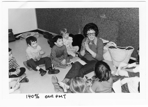 Image of Lois Lilienstein seated on the ground singing a clapping song surrounded by children.