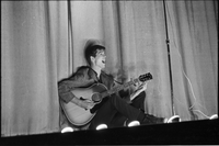 Image of a male folksinger sitting on stage singing and playing guitar at a hootenanny show at the New Yorker Theatre (out of focus).