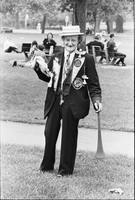 Image of an older man wearing a boater hat and suit with attached props and holding up a rubber chicken at a love-in in Queen's Park.