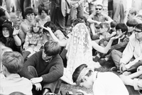 Image of a woman sitting on the grass with her hands up and head covered with a white crochet kaftan at a love-in in Queen's Park.