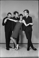 Image of the Dirty Shames rock band posing for a formal portrait with Carol Robinson in the foreground as Chick Roberts, Jim McCarthy and Amos Garrett in the background as Roberts mimes biting Robinson's arm.