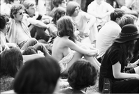 Image of a partially nude woman sitting on the grass at a love-in in Queen's Park.