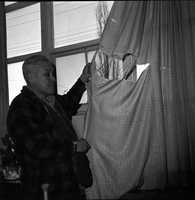 Image of a man holding up a window curtain for the camera. There is a large rip in the curtain.