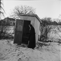 Image of a nun looking inside the open door of an outhouse in winter time in Lafontaine. Several homes are in the background.