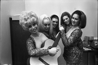 Image of the Ladybirds rock group posing for the camera in an office at Friar's Tavern with Deborah Dayan holding a guitar and Rosita Quintana pretending to tune the guitar.