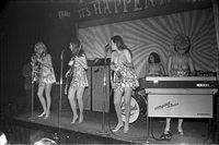 Image of the Ladybirds rock group performing topless on the stage at the Friars Tavern and Lisa Lynn and Marcelle Mitchell look to the right.