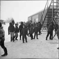 Image of young boys playing outside Sainte Croix elementary school in the winter in Lafontaine, Ontario.