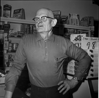 Image of an older man wearing eye glasses at a counter in a store with his left hand on his hip and posing for the camera. There are food stuffs in the background.