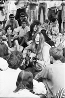 Image of a woman sitting on the grass while playing guitar and singing at a love-in in Queen's Park.