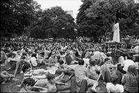 Image of the crowd watching a musician on a stage at a love-in in Queen's Park.
