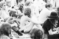 Image of a partially nude woman sitting on the grass at a love-in in Queen's Park. Photo is overexposed.