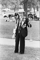 Image of an older man holding a noise maker and wearing a boater hat and suit with attached props at a love-in in Queen's Park.