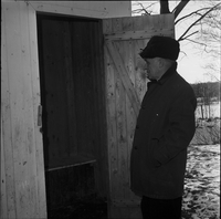 Image of an older man looking into the open door of a wooden outhouse in the winter.