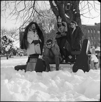 The Dirty Shames rock band posing for a photo on a bench under a tree during winter time in Queen's Park with Amos Garrett holding his ears.