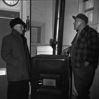 Image of two men standing next to a wood-fired heater in a classroom of a school in Lafontaine.